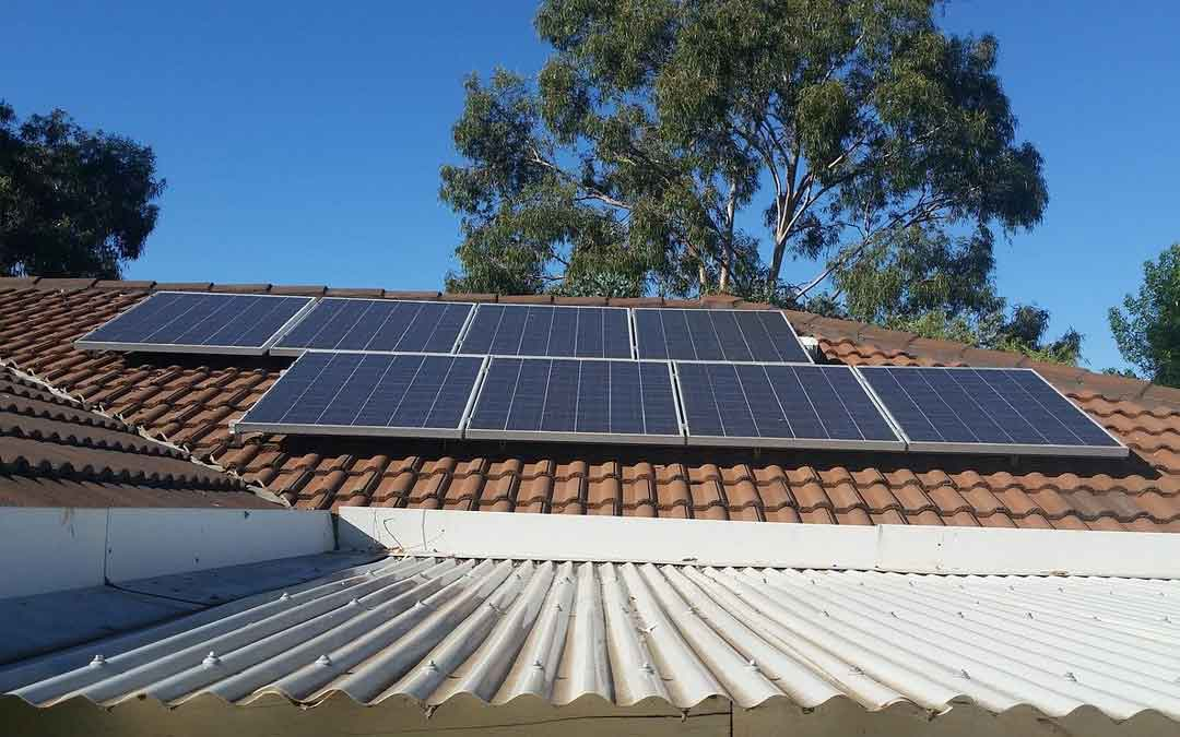 solar panels on a tiled roof with a tree in the background